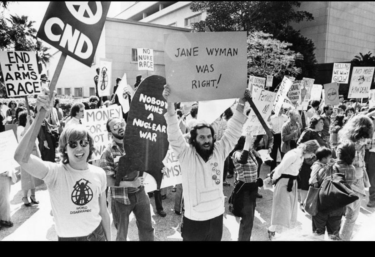 Across the street from the Music Center, demonstrators carry picket signs to protest President Reagan's policies, March 4, 19