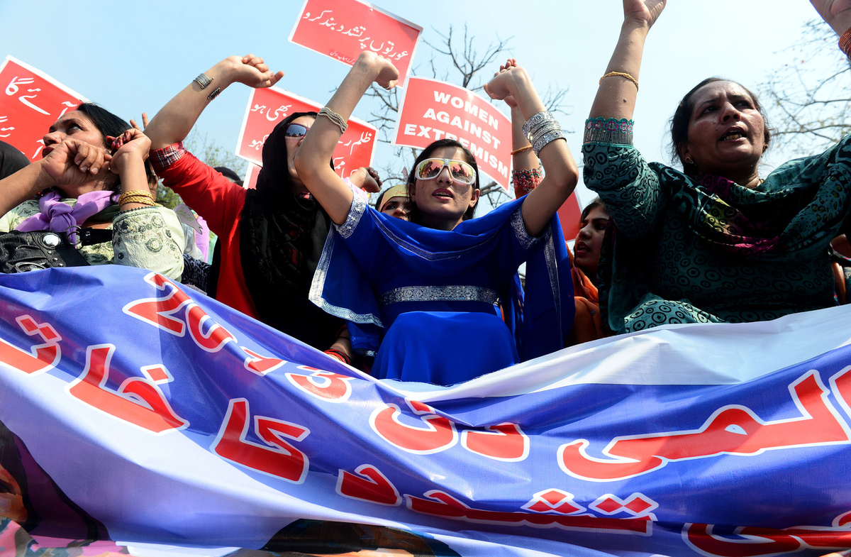 Pakistani working women carry placards as they shout slogans during a rally on International World Women's day in Lahore on M