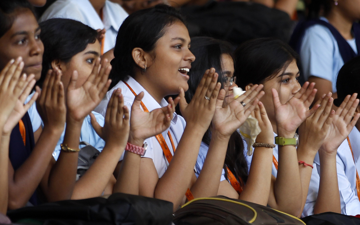 Young Indian girls clap for participants on International Women's Day celebrations organized in a college in Mumbai, India, F