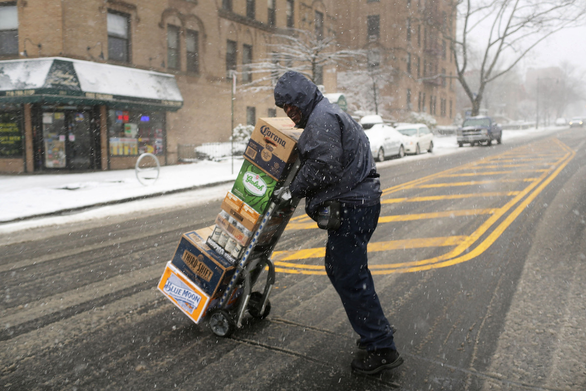 NEW YORK, NY - MARCH 08: A delivery man navigates the streets in the snow on March 8, 2013 in the Brooklyn borough of New Yor