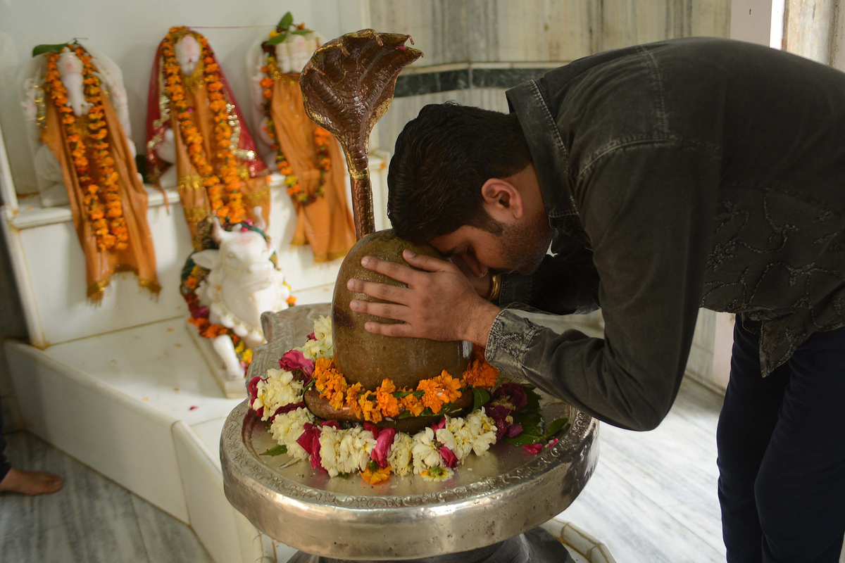 An Indian Hindu devotee pay his respects at a Shivling or idol of Lord Shiva at a temple in Amritsar on March 9, 2013 on the
