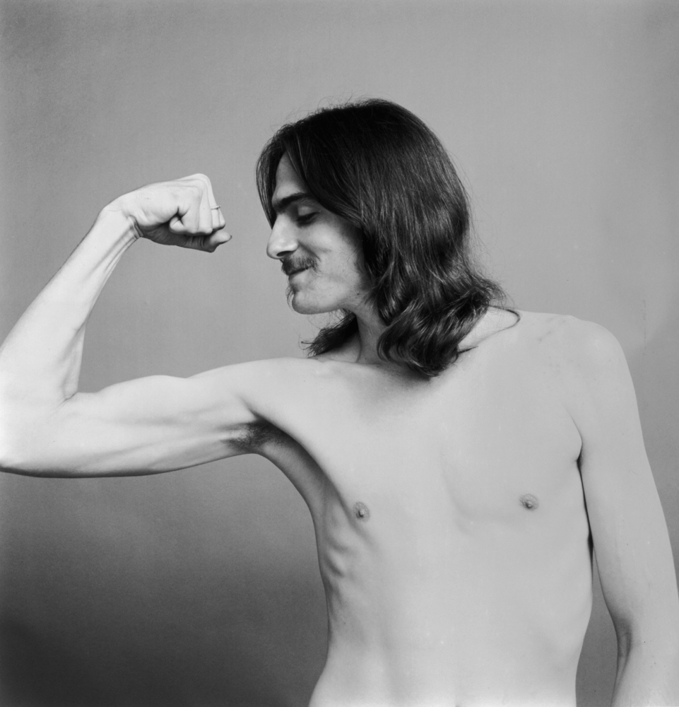 20th May 1969:  Portrait of American folk musician James Taylor making a muscle with his right arm, bare chested.  (Photo by