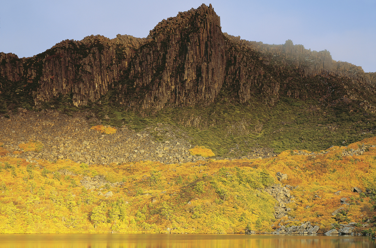 Mount Olympus, a stony 1449-meter-tall peak, rises above an Autumn flush in St. Clair National Park.