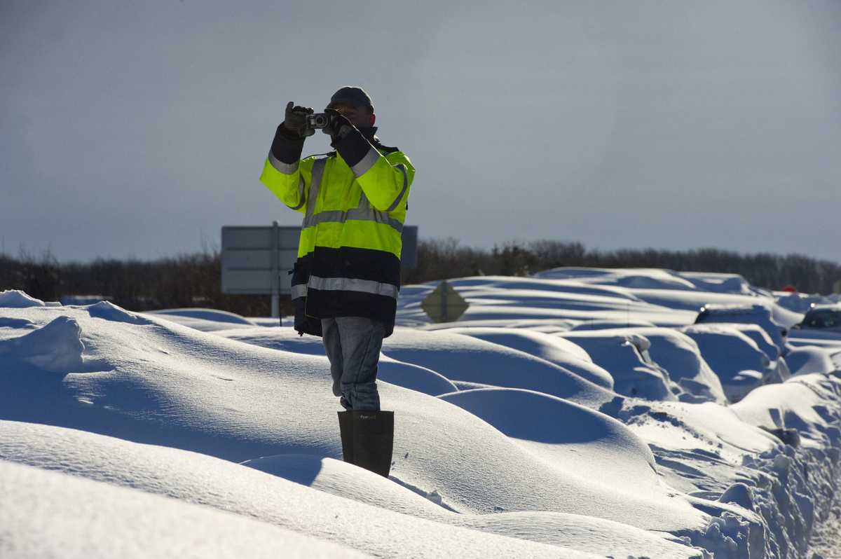 A man takes photos on March 13, 2013 perched on cars covered in snow on the D901 around Beaumont-Hague, northern France, foll