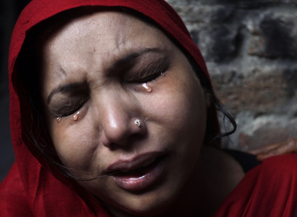 A Pakistani Christian woman weeps after visiting  her home which was damaged by an angry Muslim mob in Lahore, Pakistan, Sund