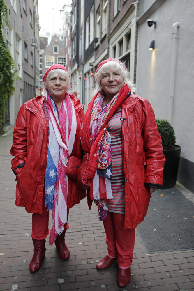 Prostitutes Martine (L) and Louise (R) Fokkens, 70, walk around the red-light district of Amsterdam on November 15, 2012, the