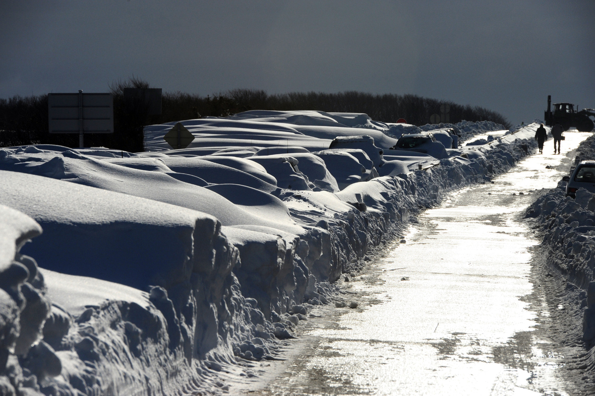 Passengers walk on March 13, 2013 by cars covered in snow on the D901 around Beaumont-Hague, northern France, following a hea