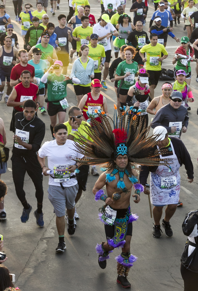 A runner dressed as a traditional Aztec dancer runs in the 28th Asics L.A. Marathon in Los Angeles Sunday March 17, 2013. The