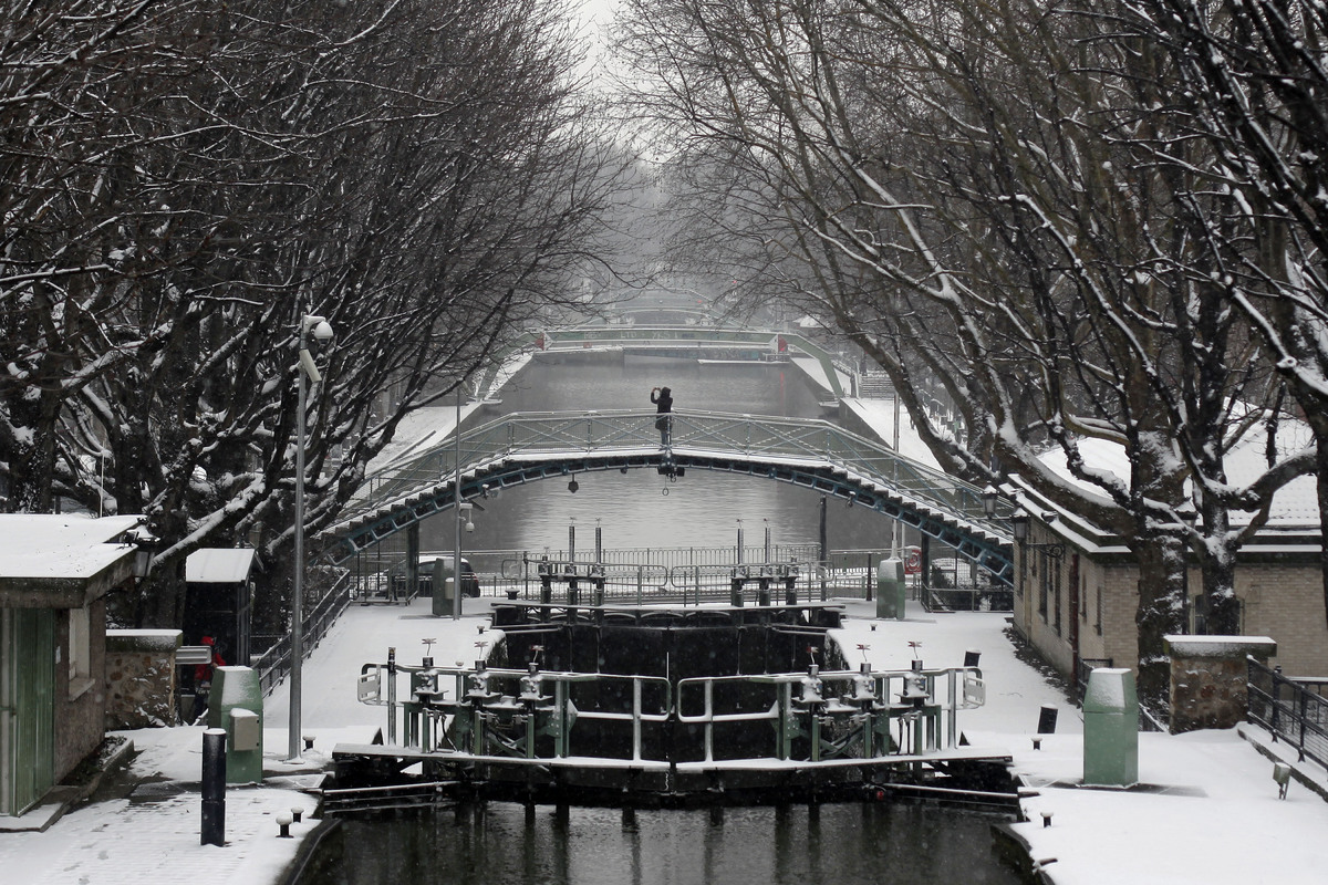 Pedestrians walk near the canal St Martin, in Paris. The snows make the cities parks seem even more elegant while making wear