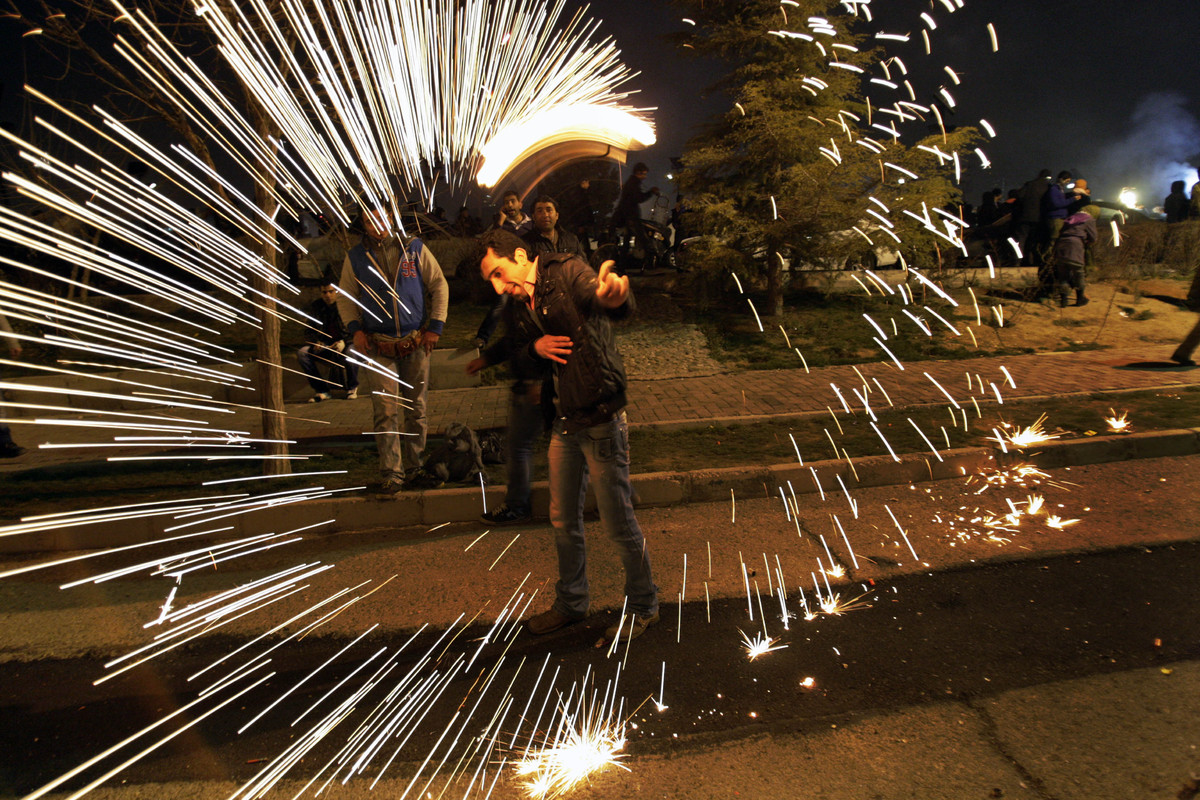 An Iranian man plays with a firework, in the Pardisan Park in Tehran, Iran, Tuesday, March 13, 2012, during Chaharshanbe Sour
