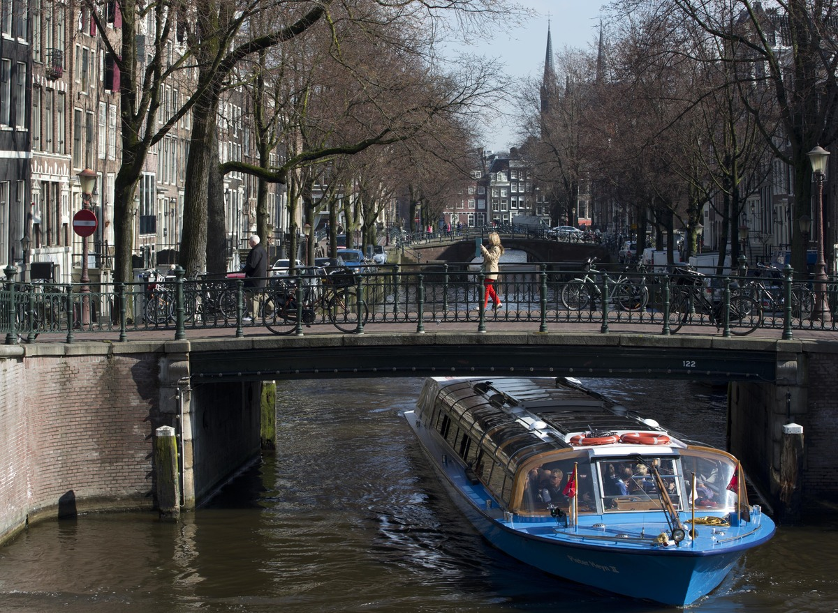 This March 18, 2013 photo shows a canal cruise boat passing under one of the bridges in Amsterdam. (AP Photo/Peter Dejong)