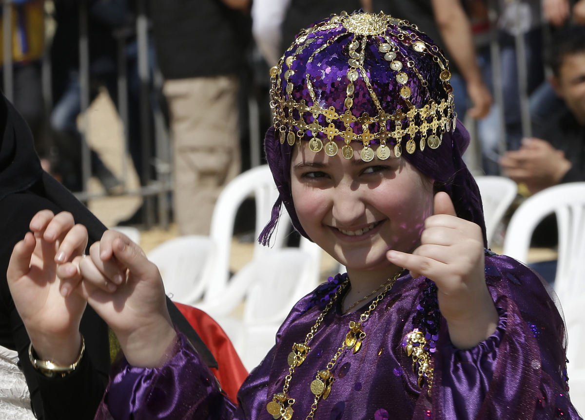 A Kurdish girl who lives in Lebanon wears traditional dress as she dances during the celebration of Nowruz day, in Beirut, Le