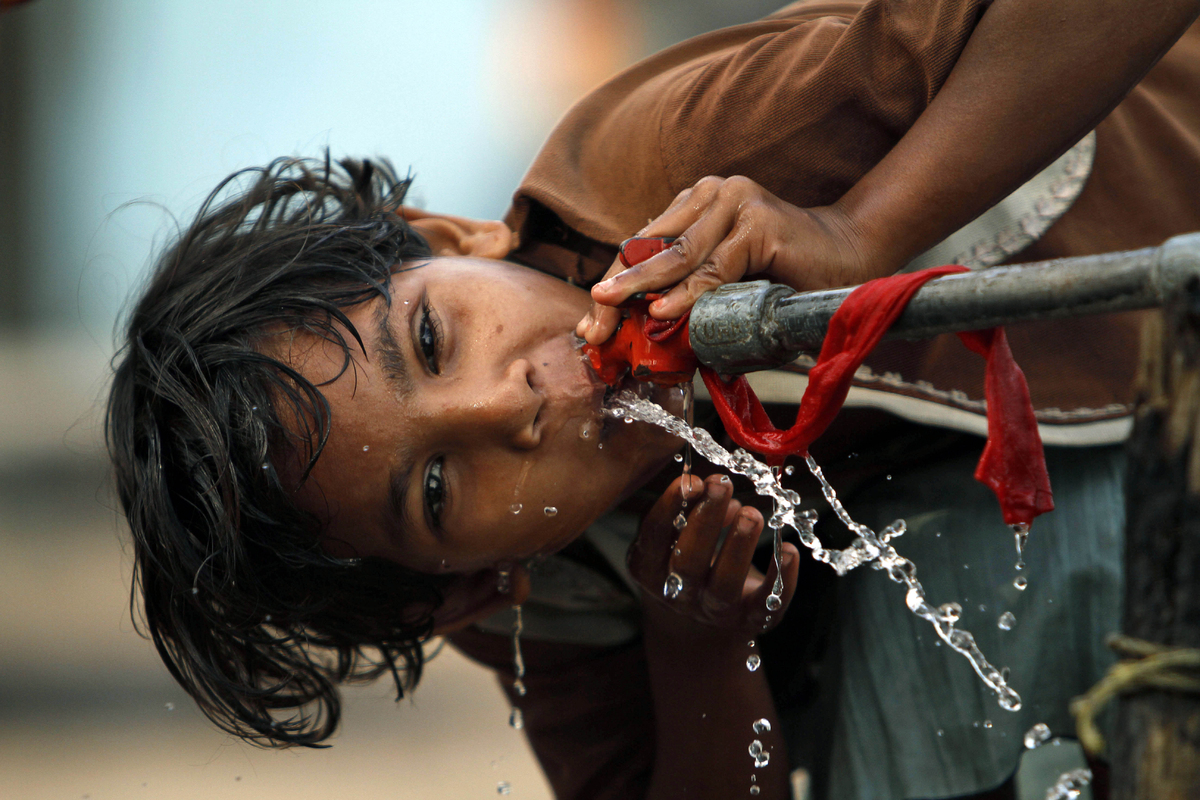 An Indian girl drinks water from a roadside tap at a slum area, on the eve of World Water Day in Allahabad, India Thursday, M