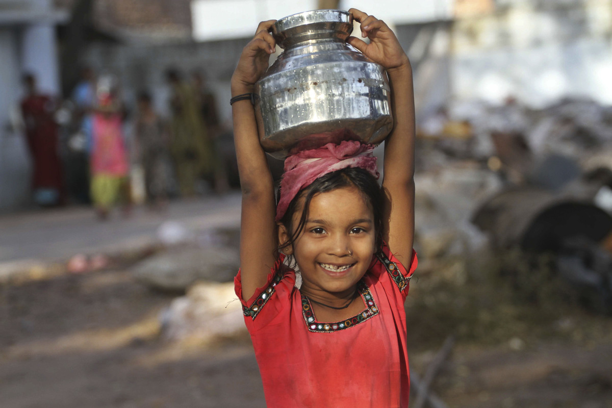 An Indian girl reacts to camera as she returns after collecting water at a slum area on the eve of World Water Day in Ahmadab
