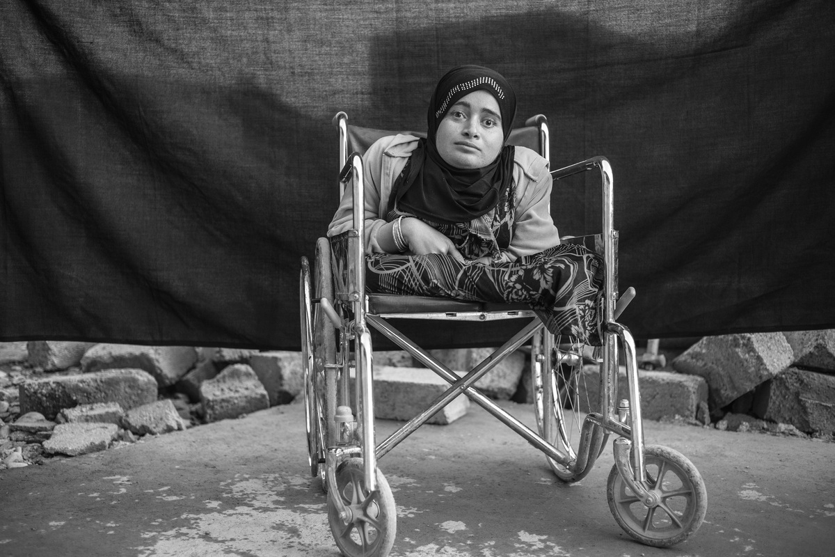 Alia sits in her wheelchair in Domiz refugee camp, in the Kurdistan Region of Iraq. The 24-year-old was living with her famil