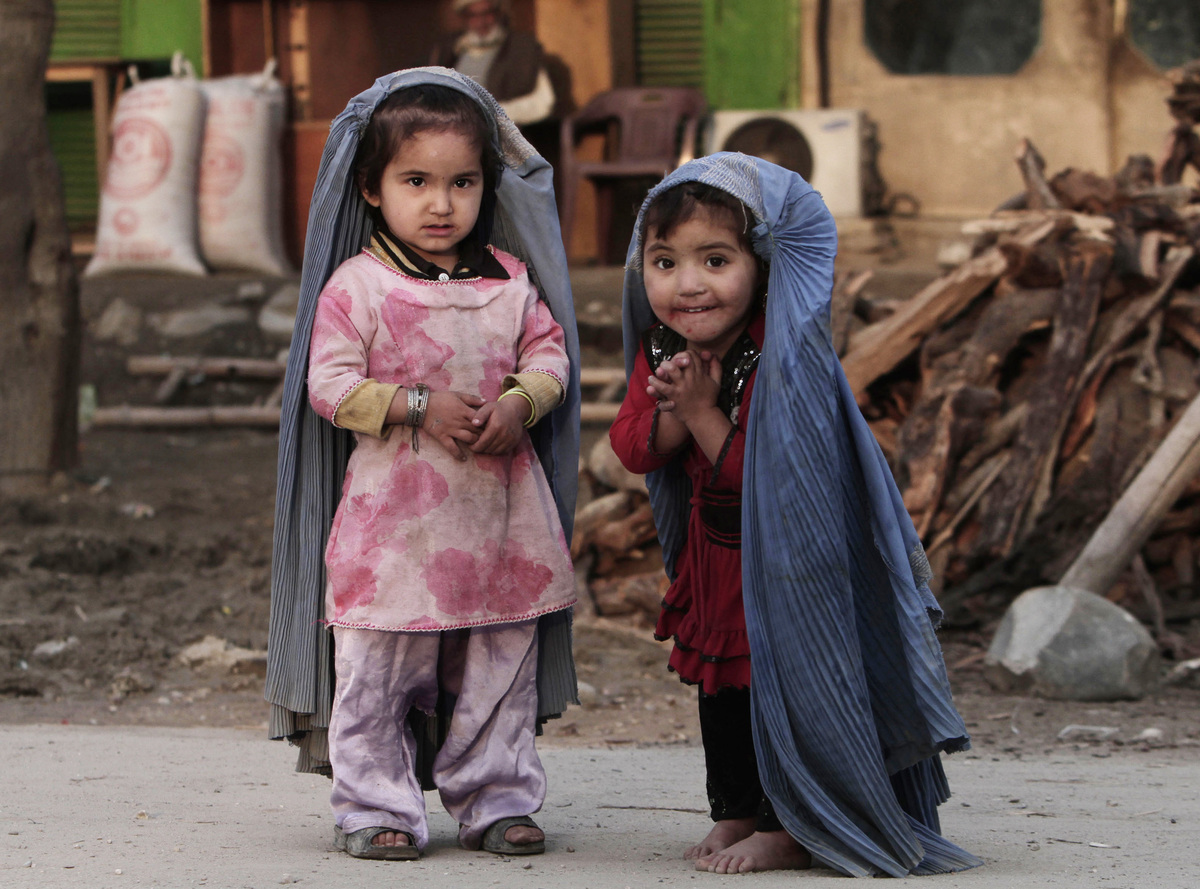 Two young girls play house, mimicking their mothers in burqas cut to their size, on the outskirts of Jalalabad, east of Kabul