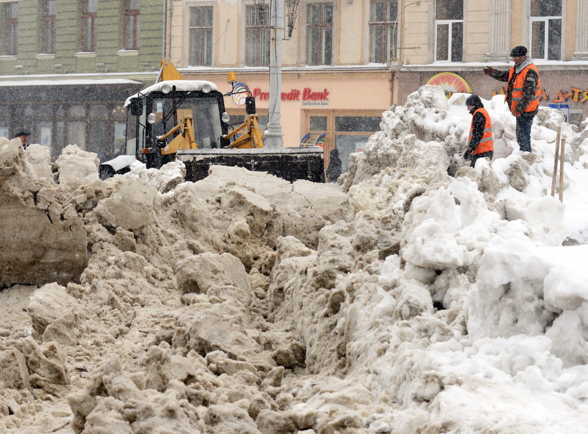 Communal workers clean snow after heavy snow fell in the western Ukrainian city of Lviv on March 22, 2013. (YURIY DYACHYSHYN/