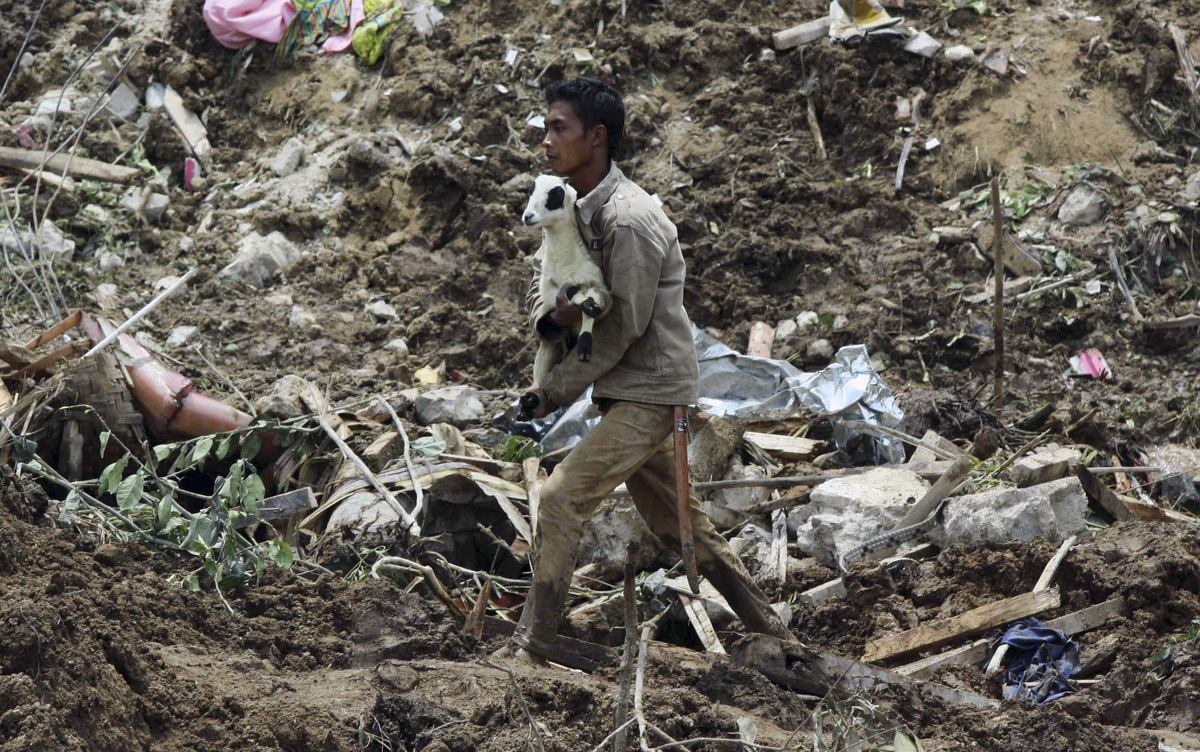 A villager carries a young goat through the mud from a landslide in Cililin, West Java, Indonesia, Monday, March 25, 2013. Re