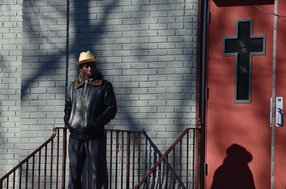 A young man waits outside the St. Catherine of Genoa Church in East Flatbush.  Kimani Gray's funeral was held in Brooklyn, NY