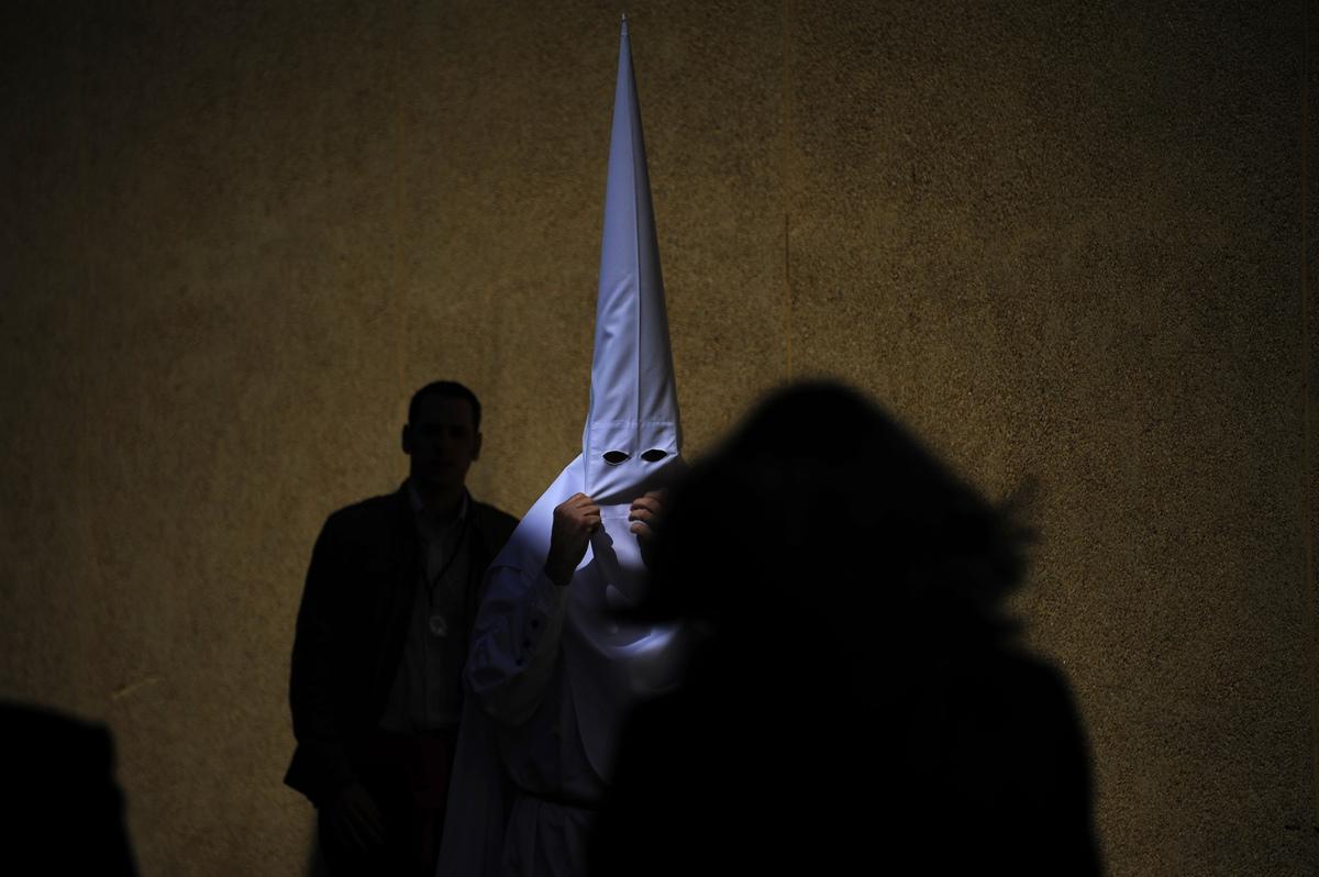 A penitent of the 'La Paz' brotherhood walks in Sevilla during the Holy Week on March 24, 2013. Christian believers around th