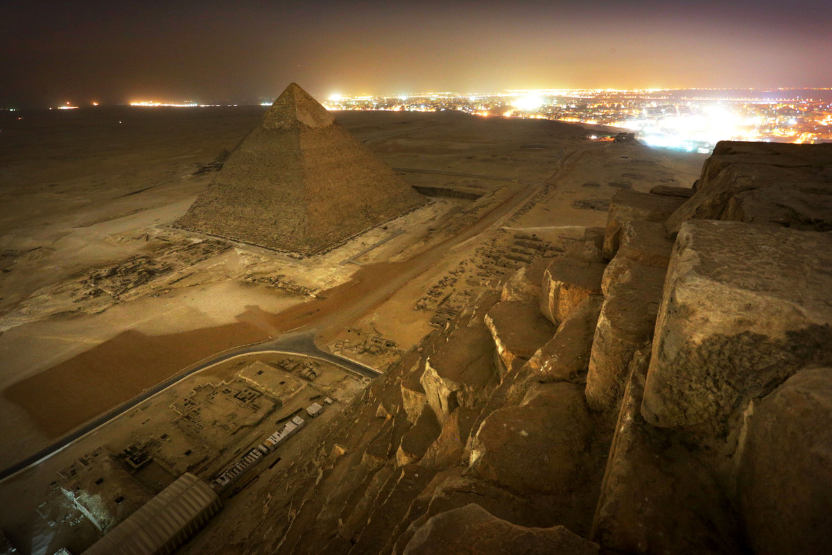 A group of tourists take photos from the top of Egypt's Great Pyramid without permission.