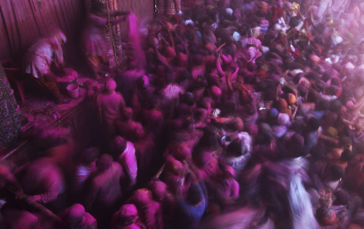 Hindu devotees are covered with colored powder inside Banke Bihari temple during Holi festival celebrations in Vrindavan, Ind
