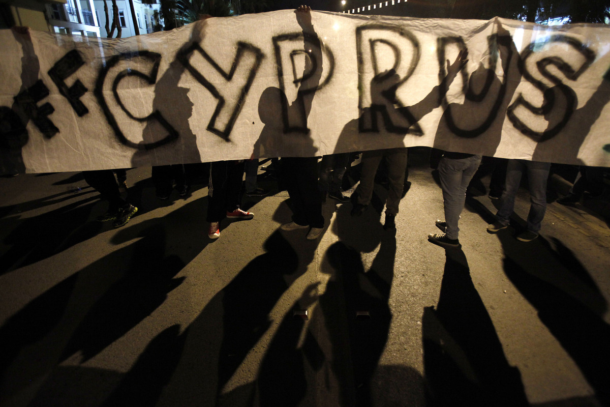 """Protesters hold a banner that reads """"Hands off Cyprus"""" during an anti-bailout rally outside European Union house in capital N"""
