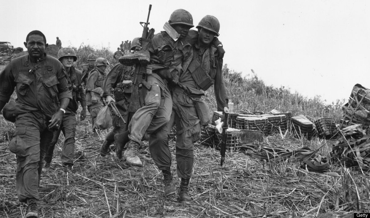 11th April 1968: US soldiers, one wounded and being carried by a colleague, walking down Hill Timothy, during the conflict in
