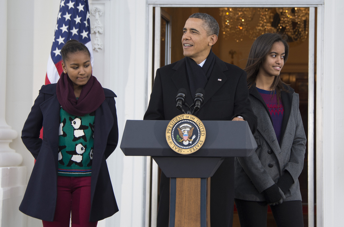 US President Barack Obama (C) gives remarks before pardoning the 2013 National Thanksgiving Turkey 'Popcorn' with is daughter