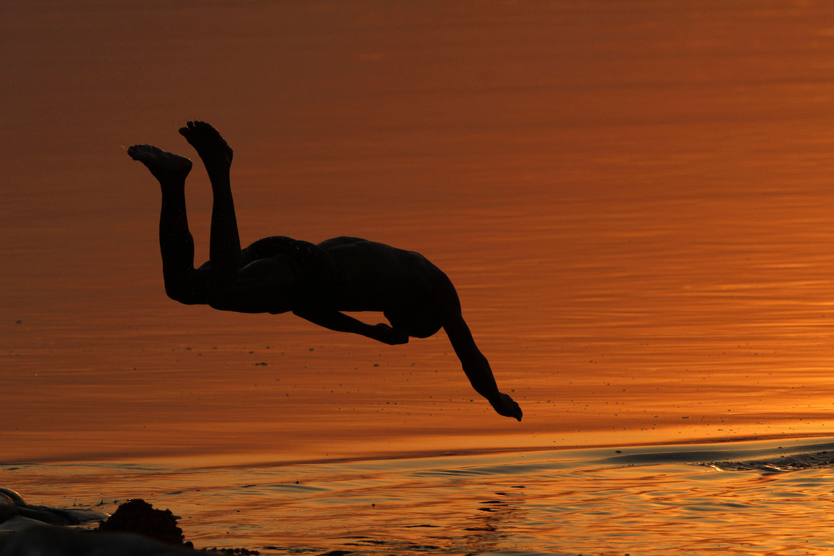 In this Wednesday, April 3, 2013 photo, an Indian boy jumps into the Ganges River in Allahabad, India. Allahabad, on the conf