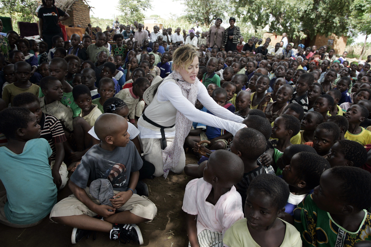 US Pop Star Madonna (C) interacts with Malawian children at Mkoko Primary School on April 2, 2013 in the region of Kasungu, c