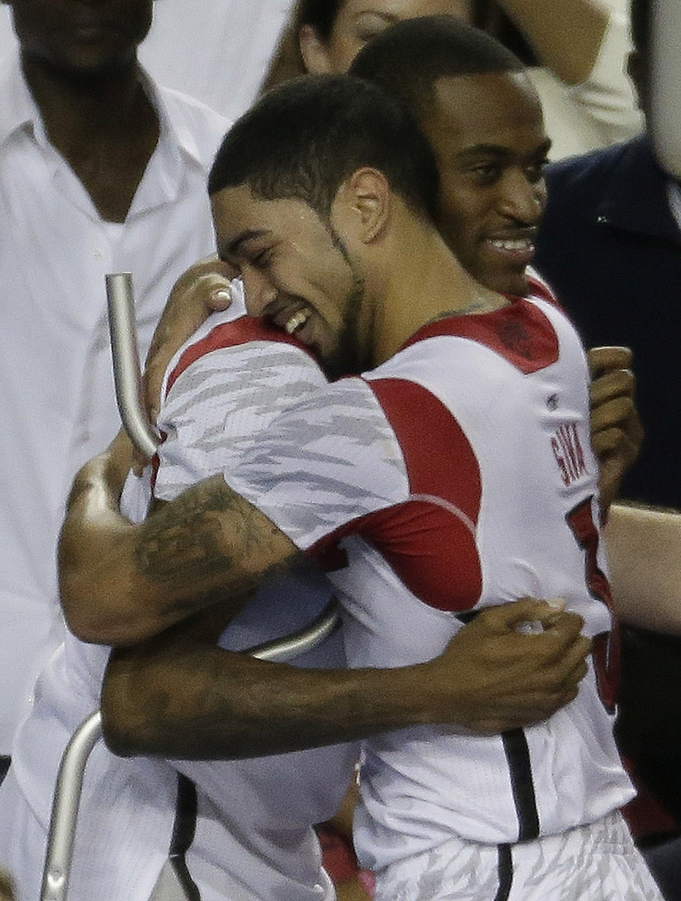 Louisville guard Kevin Ware, left, and Louisville guard Peyton Siva (3) embrace after Louisville defeated Michigan during the