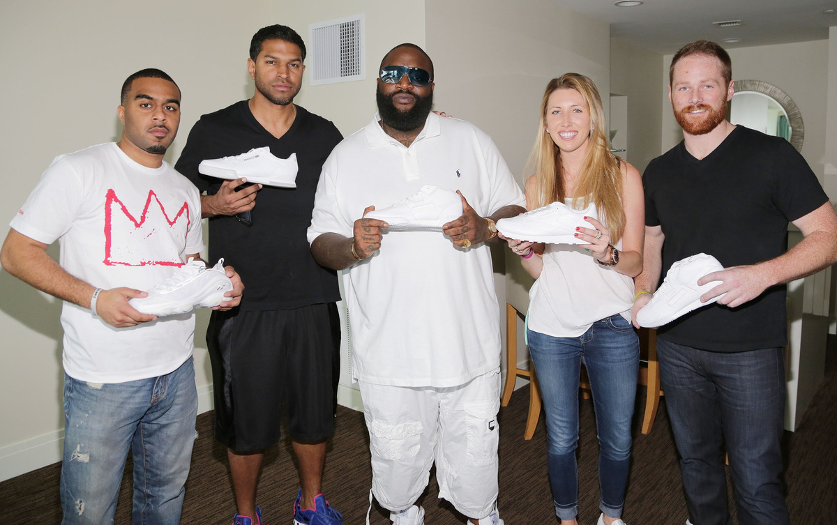 MIAMI BEACH, FL - MARCH 10: Rick Ross poses with Reebok staff members at the Reebok Classic gifting suite at Rick Ross' white