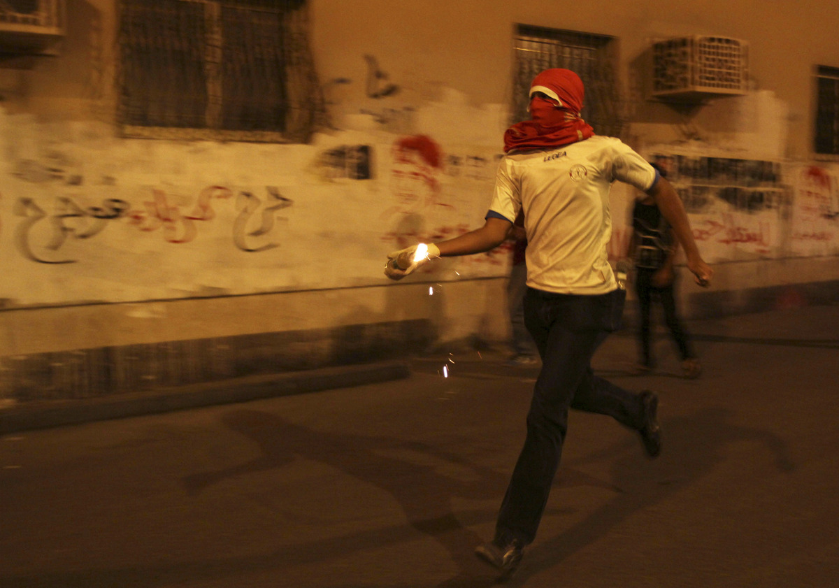 A Bahraini anti-government protester prepares to throw a petrol bomb at riot police during clashes following a rally protesti