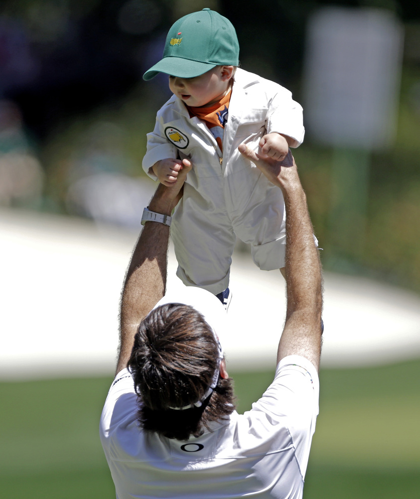 Bubba Watson lifts his son Caleb during the par three competition before the Masters golf tournament Wednesday, April 10, 201
