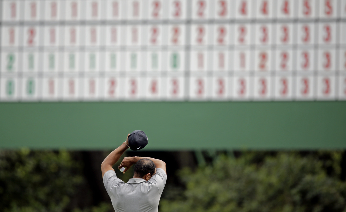 Tiger Woods wipes his forehead on the 11th green during the first round of the Masters golf tournament Thursday, April 11, 20