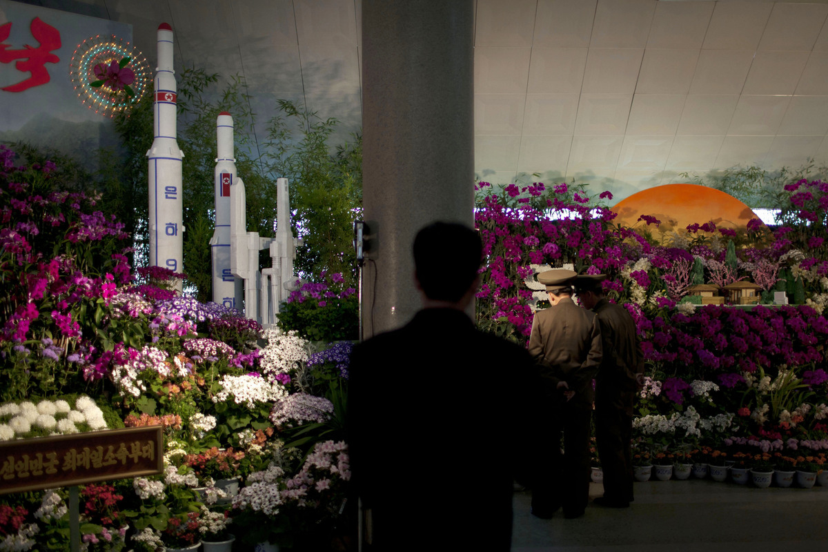 Two military officers admire displays at a flower show featuring thousands of Kimilsungia flowers, named after the late leade