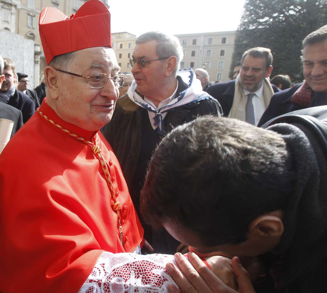 FILE - In this Feb. 18, 2012 file photo newly-appointed cardinal Giuseppe Bertello, of Italy, is congratulated by a faithful
