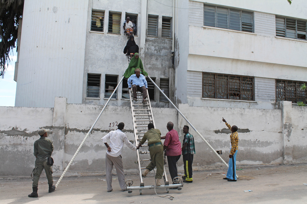 Survivors are helped to escape from a window at Mogadishu's court complex in Mogadishu, Somalia, Sunday, April 14, 2013. Mili