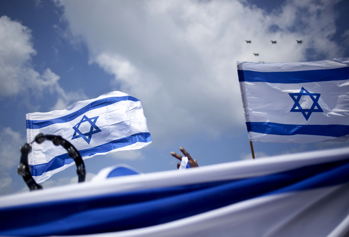 An African migrant worker holds Israeli flags during Independence Day in Tel Aviv, Tuesday, April 16, 2013. Israel is celebra