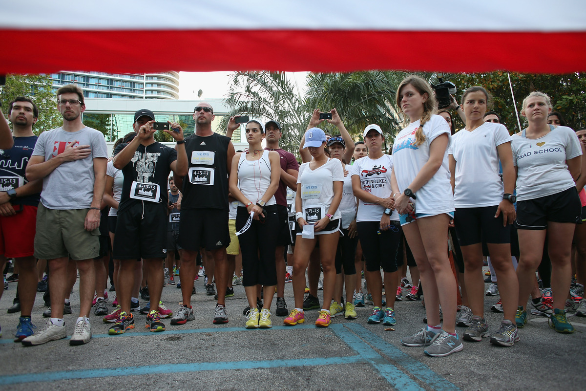 MIAMI, FL - APRIL 16: Runners stand together during the playing of the National Athem as the Baptist Health South Florida Bri