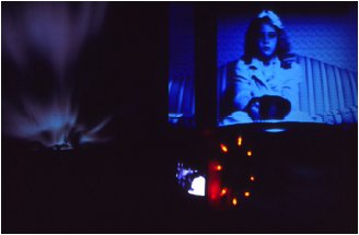 Susan Hiller Wild Talents (1997) Video installation: 3 synchronised programmes, chair, monitor, votive lights, 2 projected pr