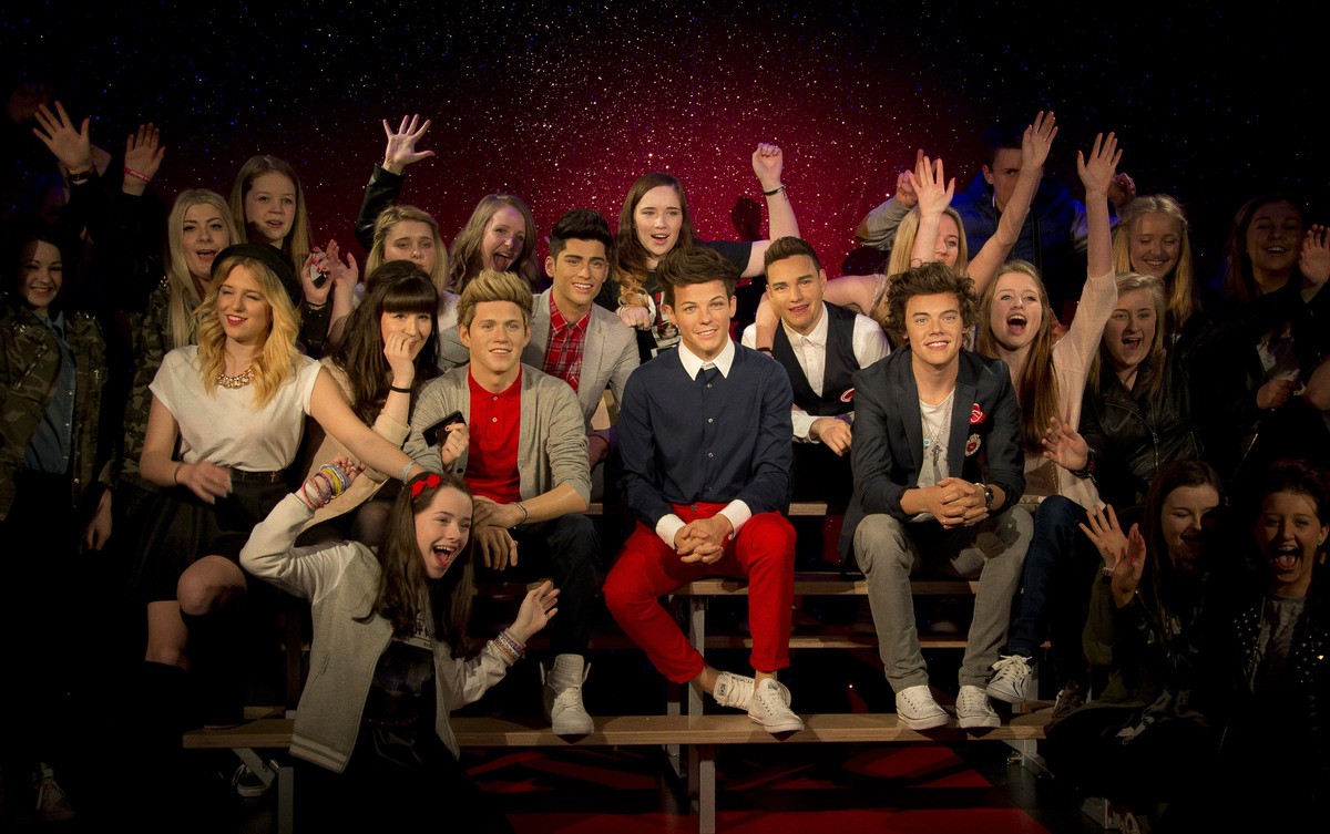 British band One Direction fans react as they pose with the new wax figure of the band, as they are revealed at Madame Tussau