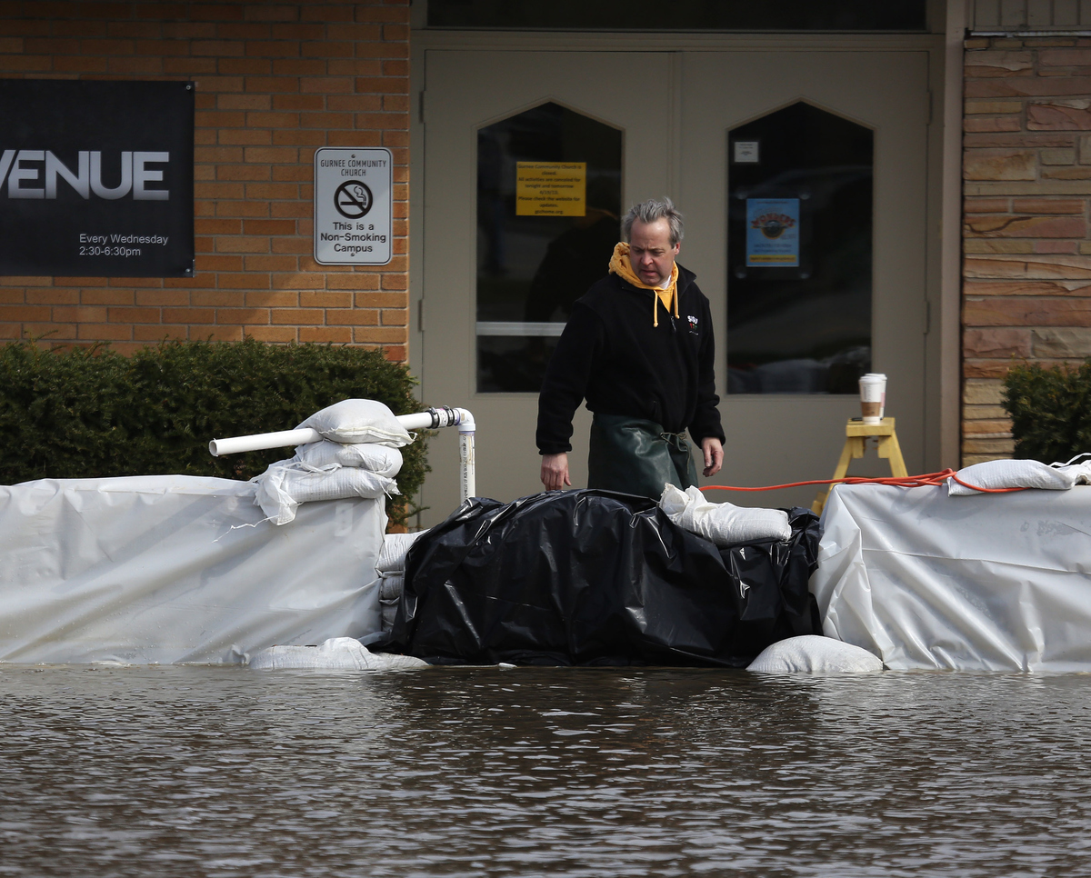 Volunteer Phil Rosborough checks the sump pumps around Gurnee Community Church after the building was surrounded by flooding