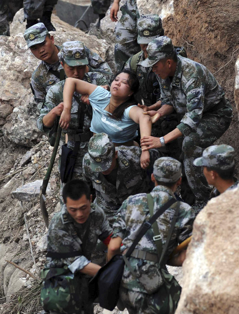In this photo released by China's Xinhua news agency, rescuers save an injured woman after an earthquake hit Baosheng Townshi