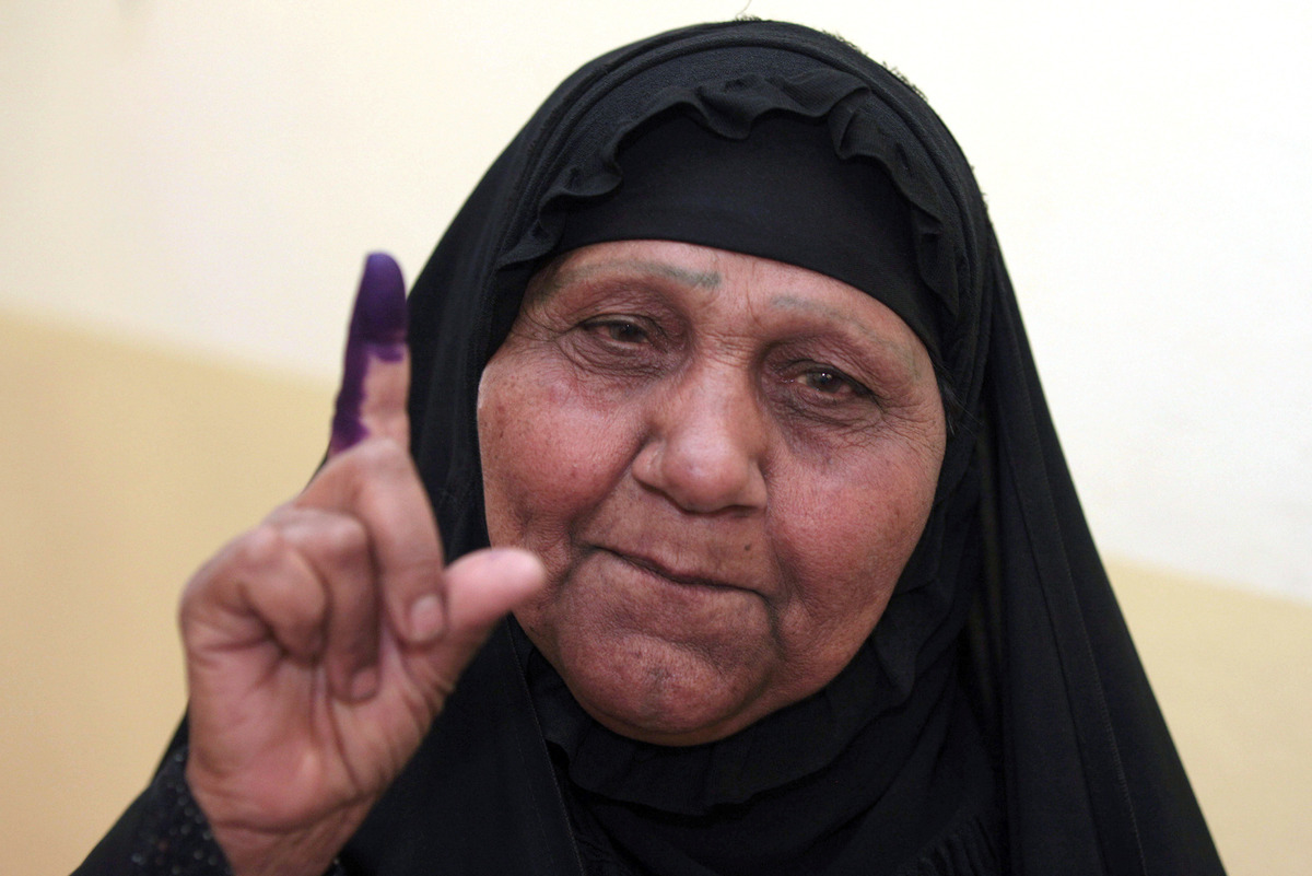 An Iraqi woman displays her ink-stained finger after voting at a polling center during the country's provincial elections in