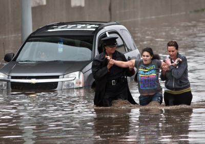 Police officer Shannon Vandenheuvel, left, and Melissa Kolenda, right, help Barbara Jones from her partially submerged car in