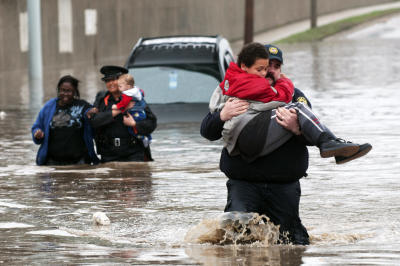 Firefighter Jason Kelley and police officer Shannon Vandenheuvel carry children from Barbara Jones' partially submerged car i