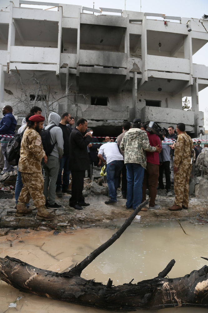 Security personnel and journalists inspect the site of a car bomb that targeted the French embassy wounding two French guards