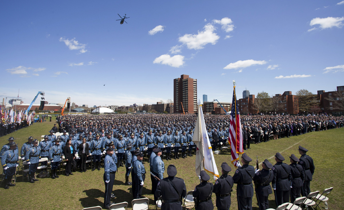 This photo provided by Massachusetts Institute of Techonology, helicopters fly over law enforcement officers assembled at a m